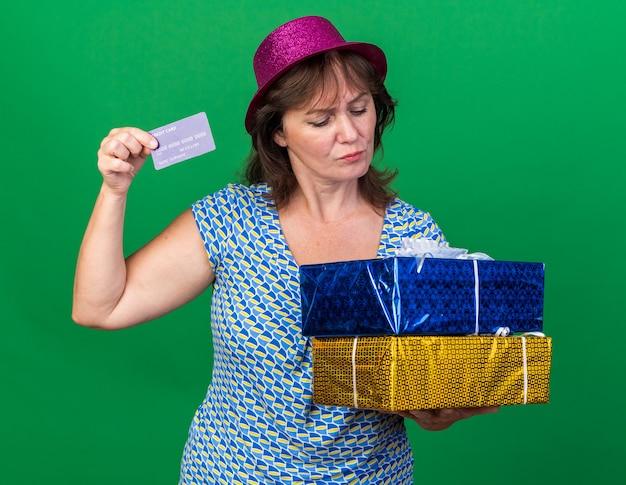 Vrouw van middelbare leeftijd in feestmuts met verjaardagscadeautjes en creditcard die er verward uitziet om een verjaardagsfeestje te vieren dat over de groene muur staat