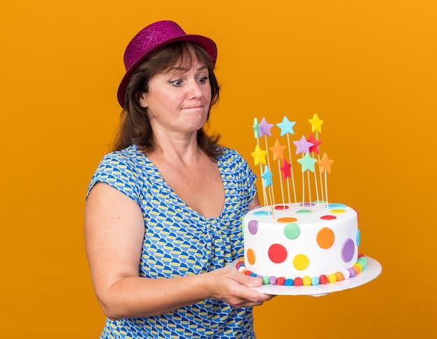 Vrouw van middelbare leeftijd in feestmuts met verjaardagstaart die ernaar kijkt met een verwarde uitdrukking die een verjaardagsfeestje viert dat over een oranje muur staat