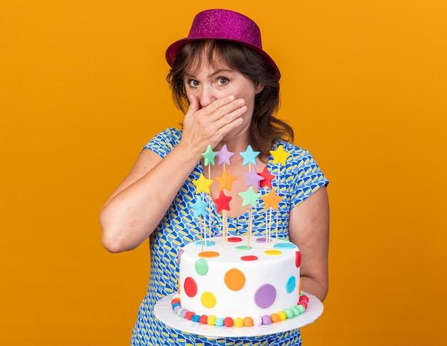 Vrouw van middelbare leeftijd in feestmuts met verjaardagstaart die geschokt is en mond bedekt met hand die verjaardagsfeestje viert dat over oranje muur staat