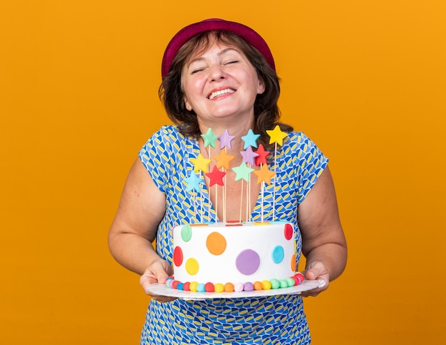 Vrouw van middelbare leeftijd in feestmuts met verjaardagstaart glimlachend vrolijk blij en opgewonden om verjaardagsfeestje te vieren dat over oranje muur staat