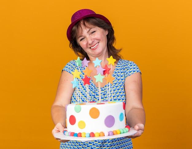 Vrouw van middelbare leeftijd in feestmuts met verjaardagstaart met een glimlach op het gezicht, gelukkig en vrolijk vierend verjaardagsfeestje staande over oranje muur