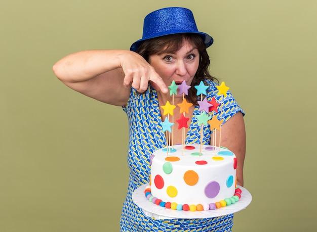Vrouw van middelbare leeftijd in feestmuts met verjaardagstaart wijzend met wijsvinger erop blij en verrast om verjaardagsfeestje te vieren dat over groene muur staat