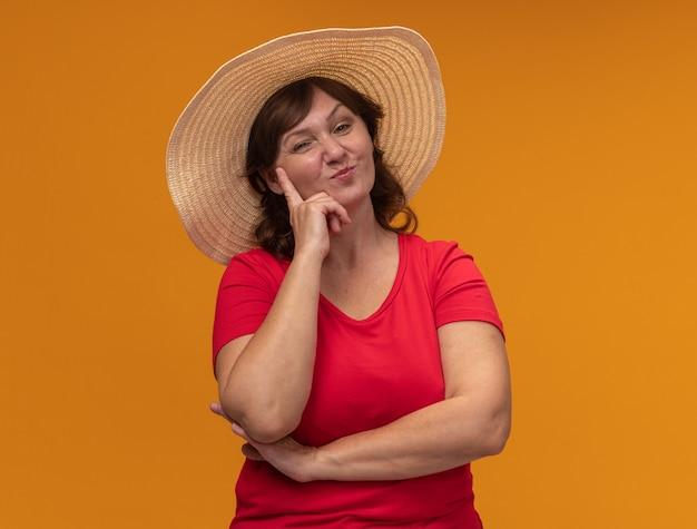 Vrouw van middelbare leeftijd in rode t-shirt en zomerhoed met blij gezicht lachend staande over oranje muur