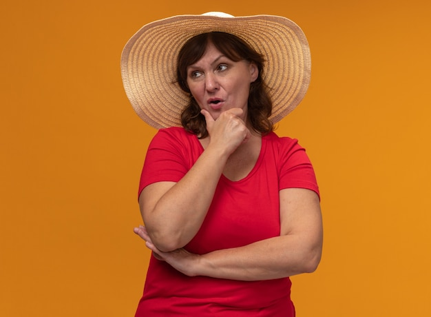 Vrouw van middelbare leeftijd in rode t-shirt en zomerhoed opzij kijken met peinzende uitdrukking denken staande over oranje muur