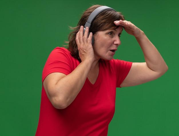 Vrouw van middelbare leeftijd in rode t-shirt met koptelefoon op zoek ver weg met hand boven het hoofd staande over groene muur