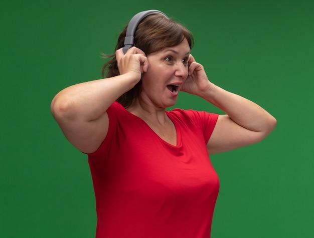 Vrouw van middelbare leeftijd in rode t-shirt met koptelefoon opzij kijken blij en verrast staande over groene muur
