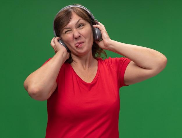 Vrouw van middelbare leeftijd in rode t-shirt met koptelefoon uitsteekt tong blij en blij staande over groene muur