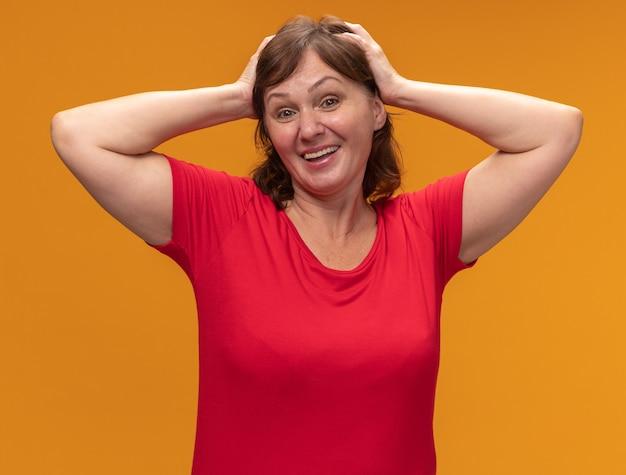Vrouw van middelbare leeftijd in rood t-shirt gelukkig en positief met handen op haar hoofd die zich over oranje muur bevinden