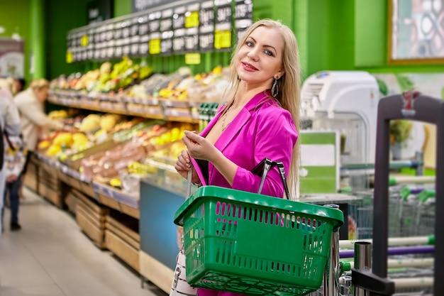 Vrouw van middelbare leeftijd in roze staat in de supermarkt met een winkelmandje in handen.