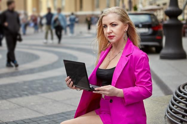 Vrouw van middelbare leeftijd in roze zit op bankje met laptop in handen op drukke straat van de stad.