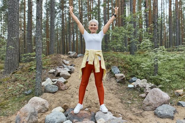 Vrouw van middelbare leeftijd in sportkleding en loopschoenen die zich uitstrekt