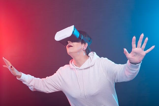 Vrouw van middelbare leeftijd in trui kijkt naar nieuwe film met een bril van virtual reality