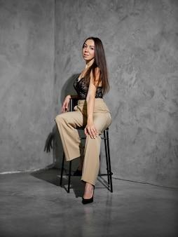 Vrouw van middelbare leeftijd in wijde broek zittend op de stoel in de hoek van de kamer