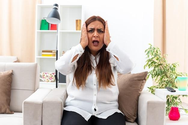 Vrouw van middelbare leeftijd in wit overhemd en zwarte broek gefrustreerd met handen op haar hoofd zittend op de stoel in lichte woonkamer
