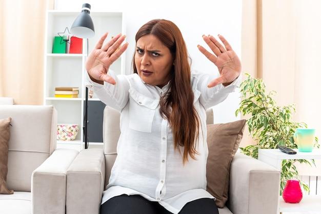 Vrouw van middelbare leeftijd in wit overhemd en zwarte broek met serieus gezicht die een stopgebaar maakt met handen zittend op de stoel in lichte woonkamer
