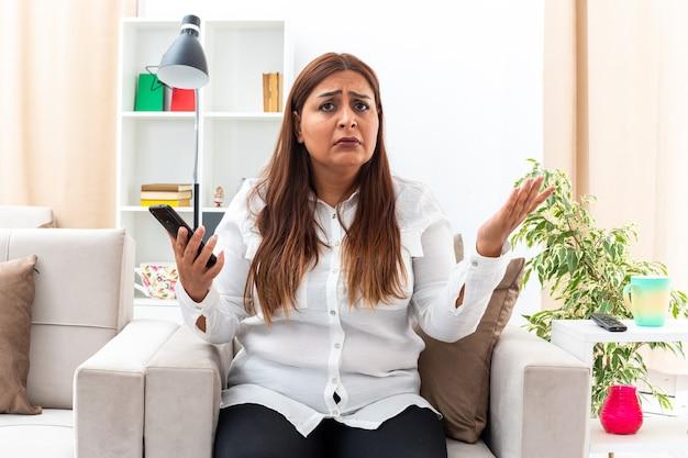 Vrouw van middelbare leeftijd in wit overhemd en zwarte broek met smartphone verward en ontevreden zittend op de stoel in lichte woonkamer