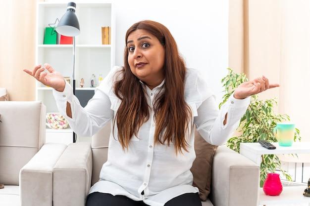 Vrouw van middelbare leeftijd in wit overhemd en zwarte broek verwarde armen naar de zijkanten spreidend zonder antwoord op de stoel in lichte woonkamer