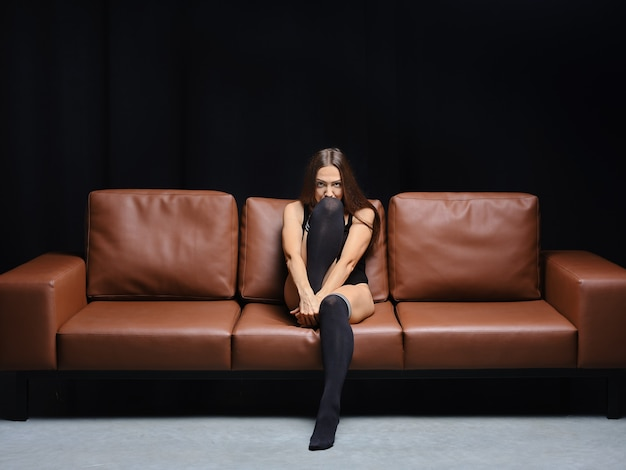 Vrouw van middelbare leeftijd in zwarte bodysuit en overknee warme sokken zit op leren bank