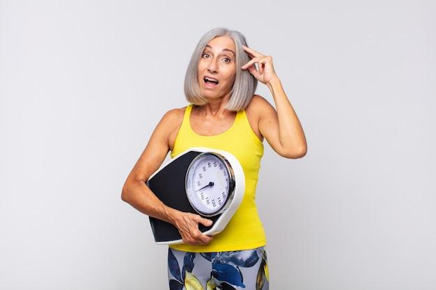 Vrouw van middelbare leeftijd kijkt blij, verbaasd en verrast, glimlachend