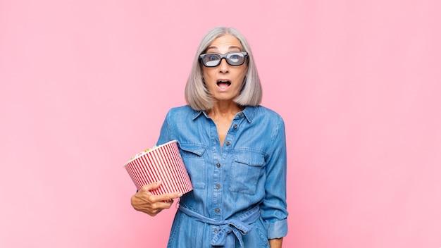Vrouw van middelbare leeftijd kijkt erg geschokt of verrast, starend met open mond en zegt wow-filmconcept