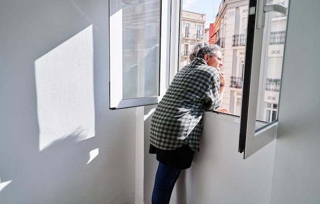 Vrouw van middelbare leeftijd kijkt uit het raam op een zonnige dag