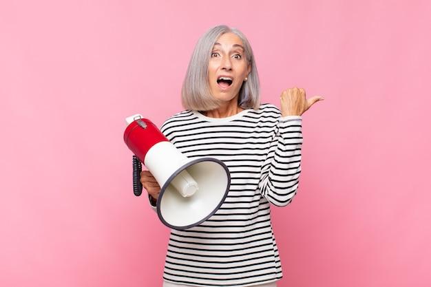 Vrouw van middelbare leeftijd kijkt verbaasd van ongeloof, wijst naar een voorwerp op de zijkant en zegt wow, ongelooflijk met een megafoon
