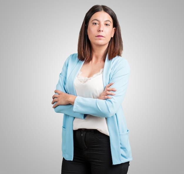 Vrouw van middelbare leeftijd kruising zijn armen, serieus en opleggen, zich zelfverzekerd voelen en macht tonen