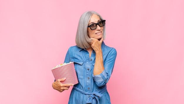 Vrouw van middelbare leeftijd lachend met een gelukkige, zelfverzekerde uitdrukking met hand op de kin, zich afvragend en op zoek naar het zijfilmconcept