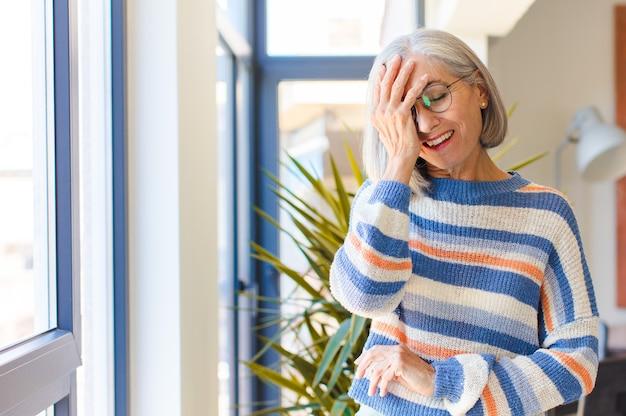 Vrouw van middelbare leeftijd lacht en slaat voorhoofd, zoals oh zeggen! ik was het vergeten of dat was een domme fout
