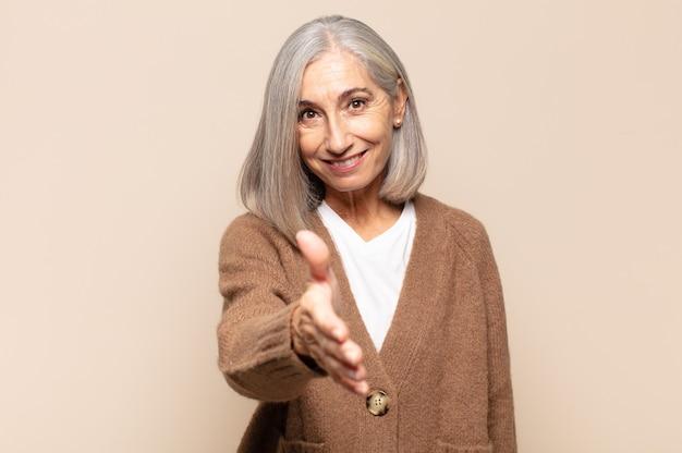 Vrouw van middelbare leeftijd lacht, ziet er gelukkig, zelfverzekerd en vriendelijk uit, biedt een handdruk om een deal te sluiten, werkt samen