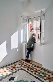 Vrouw van middelbare leeftijd leunt uit het raam in een kamer met gekleurde hydraulische vloeren
