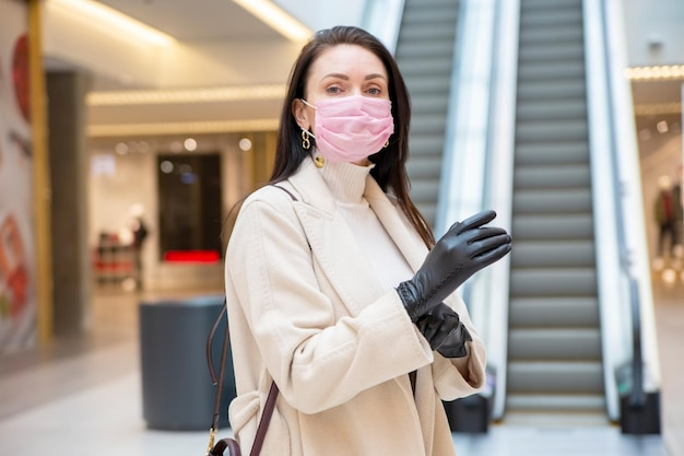 Vrouw van middelbare leeftijd met beschermend gezichtsmasker die handschoenen aantrekt tegen de achtergrond van een openbare plaats