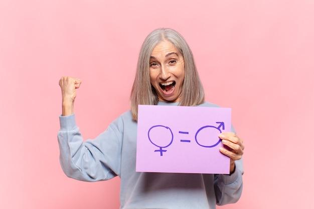 Vrouw van middelbare leeftijd met een bordje met het symbool voor gendergelijkheid