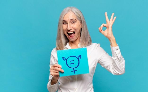 Vrouw van middelbare leeftijd met een briefje met symbool voor gendergelijkheid