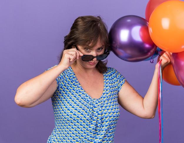 Vrouw van middelbare leeftijd met een bril die een bos kleurrijke ballonnen vasthoudt en een bril afzet met een verdachte uitdrukking