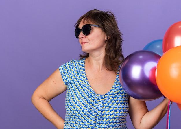 Vrouw van middelbare leeftijd met een bril die een stel kleurrijke ballonnen vasthoudt en opzij kijkt met een serieus gezicht dat een verjaardagsfeestje viert dat over een paarse muur staat