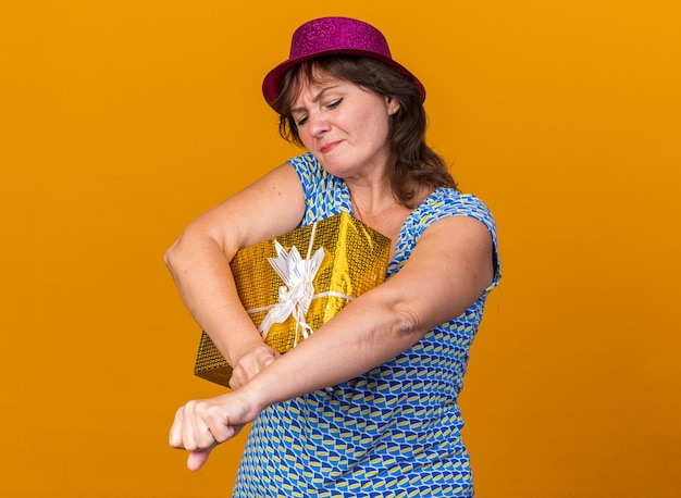 Vrouw van middelbare leeftijd met een feesthoed die een cadeau vasthoudt en er verward en ontevreden uitziet om een verjaardagsfeestje te vieren dat over de oranje muur staat