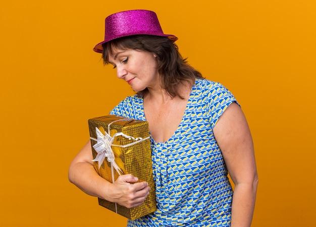 Vrouw van middelbare leeftijd met een feesthoed die een cadeautje vasthoudt en neerkijkt met een verlegen glimlach op het gezicht