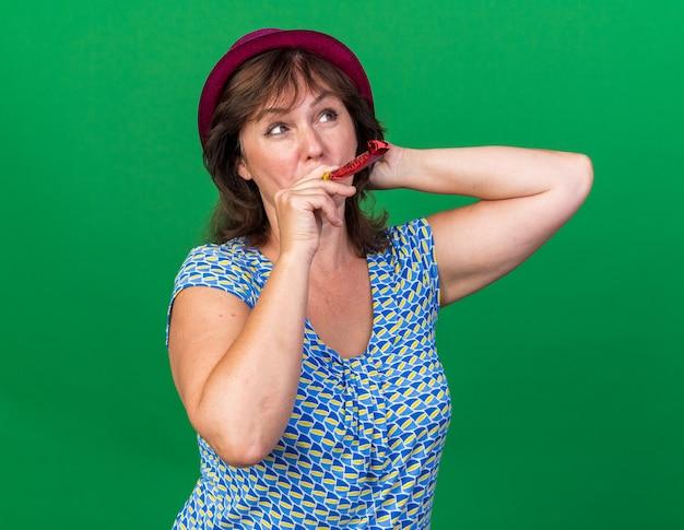Vrouw van middelbare leeftijd met een feesthoed die een fluitje vasthoudt en omhoog kijkt met een glimlach op het gezicht en viert een verjaardagsfeestje dat over de groene muur staat