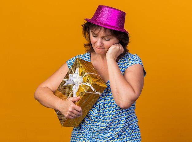 Vrouw van middelbare leeftijd met een feestmuts die een cadeautje vasthoudt en ernaar kijkt verbaasd verjaardagsfeestje vieren dat over de oranje muur staat