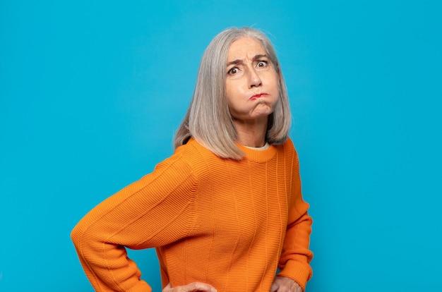 Vrouw van middelbare leeftijd met een gekke, gekke, verbaasde uitdrukking, puffende wangen, zich gevuld, dik en vol eten