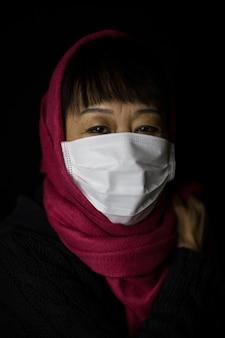 Vrouw van middelbare leeftijd met een kastanjebruine hijab die een gezichtsmasker draagt op zwarte achtergrond - coronavirus-concept