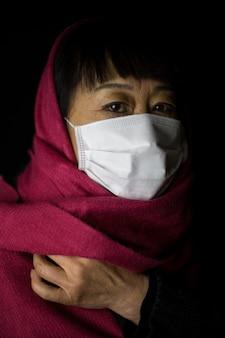 Vrouw van middelbare leeftijd met een kastanjebruine hijab die een gezichtsmasker op zwart draagt