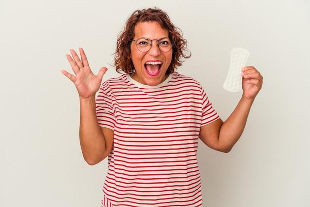 Vrouw van middelbare leeftijd met een kompres geïsoleerd op een witte achtergrond die een aangename verrassing ontvangt, opgewonden en handen opsteekt.