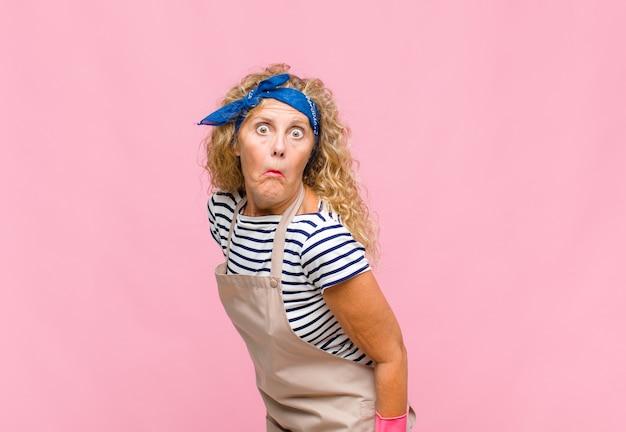 Vrouw van middelbare leeftijd met een maffe, gekke, verbaasde uitdrukking, puffende wangen, zich gevuld, dik en vol met voedselhuishoudster
