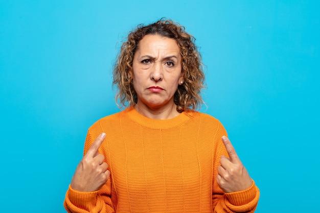 Vrouw van middelbare leeftijd met een slechte houding die er trots en agressief uitziet, naar boven wijst of een leuk teken maakt met handen