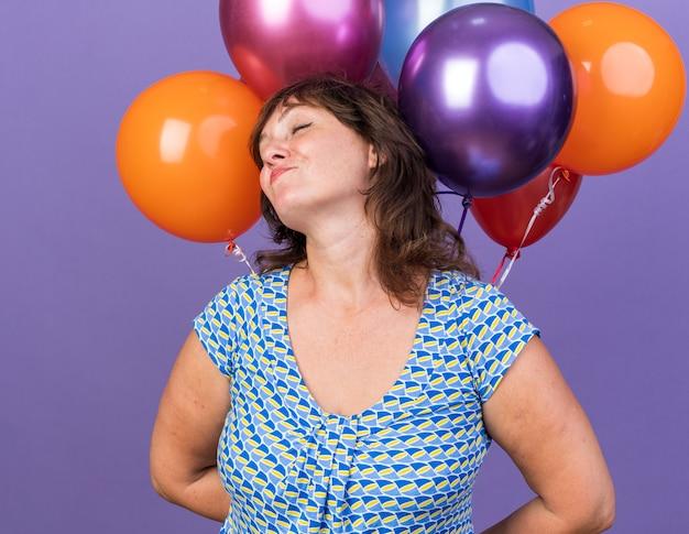 Vrouw van middelbare leeftijd met een stel kleurrijke ballonnen, blij en tevreden glimlachend, vrolijk verjaardagsfeestje vierend dat over de paarse muur staat
