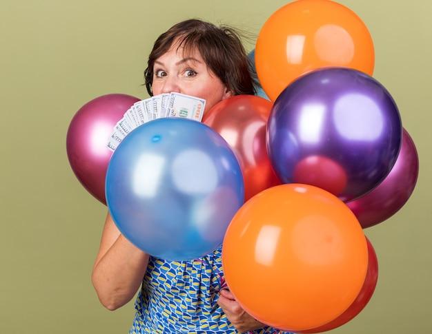 Vrouw van middelbare leeftijd met een stel kleurrijke ballonnen die contant geld vasthoudt, verrast om een verjaardagsfeestje te vieren dat over de groene muur staat
