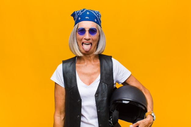 Vrouw van middelbare leeftijd met een vrolijke, zorgeloze, rebelse houding, grappen maken en tong uitsteken, plezier maken