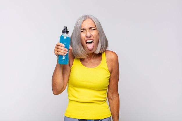 Vrouw van middelbare leeftijd met een vrolijke, zorgeloze, rebelse houding